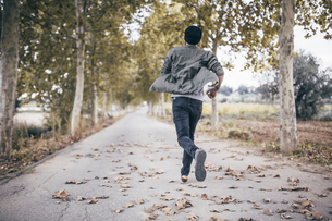 Spain, Tarragona, back view of young man running on autumnalの写真素材 [FYI04344091]