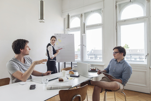 Three creative business people having a meeting in a modernの写真素材 [FYI04344104]