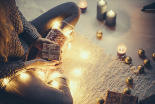 Woman sitting with Christmas present and fairy lights on theの写真素材 [FYI04344143]
