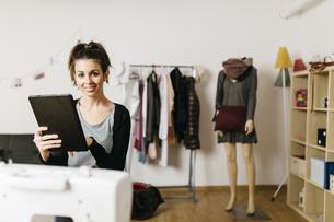 Young fashion designer working in her studio, using digitalの写真素材 [FYI04344152]