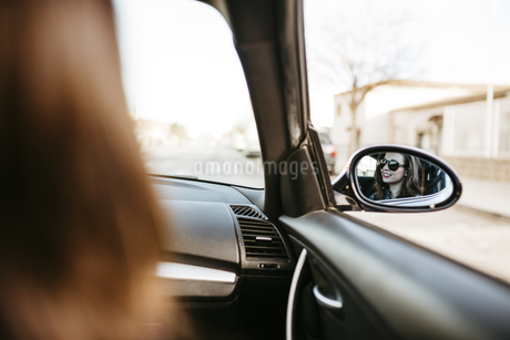 Female front passanger in car reflected in car mirrorの写真素材 [FYI04344160]