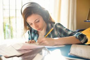 Young woman wearing headphones writing on music sheetの写真素材 [FYI04344183]