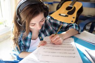 Young woman wearing headphones writing on music sheetの写真素材 [FYI04344184]