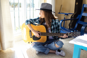 Young woman sitting on the floor playing guitarの写真素材 [FYI04344185]