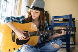Smiling young woman playing guitar indoorsの写真素材 [FYI04344187]