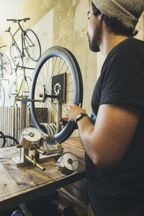 Mechanic working on tire in a custom-made bicycle storeの写真素材 [FYI04344192]
