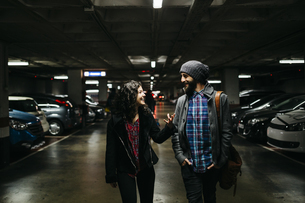 Smiling young couple talking in a parking garageの写真素材 [FYI04344202]