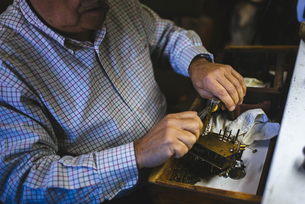Watchmaker hands in the foreground working with an antique cの写真素材 [FYI04344221]