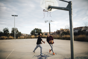 Two young men playing basketball on an outdoor courtの写真素材 [FYI04344236]