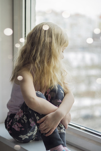 Blond little girl sitting on window sill looking through winの写真素材 [FYI04344247]
