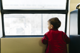Back view of little boy on his first train ride looking throの写真素材 [FYI04344270]
