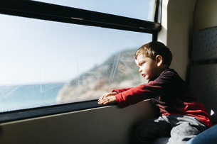 Little boy on his first train ride looking through the windoの写真素材 [FYI04344272]