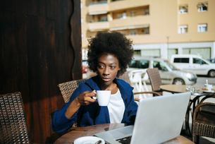 Young woman with laptop sitting in a street cafe drinking coの写真素材 [FYI04344331]