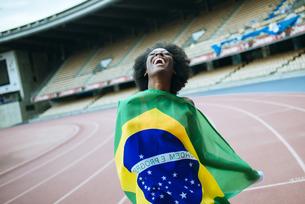 Young black athlete in stadium carrying Brazilian flagの写真素材 [FYI04344341]