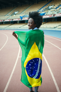 Young black athlete in stadium carrying Brazilian flagの写真素材 [FYI04344342]