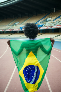 Young black athlete in stadium carrying Brazilian flagの写真素材 [FYI04344343]