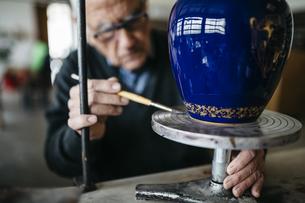 Senior man decorating ceramic vase in his spare timeの写真素材 [FYI04344377]