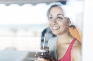 Smiling young woman holding mug with healthy drinkの写真素材 [FYI04344401]