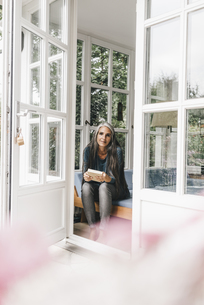 Smiling woman with book sitting on lounge in her winter gardの写真素材 [FYI04344645]