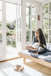 Woman sitting on lounge in winter garden reading bookの写真素材 [FYI04344648]