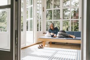 Woman lying on lounge in winter garden reading e-bookの写真素材 [FYI04344651]