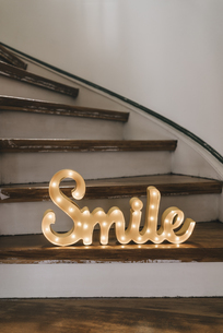 Shining word 'Smile' on wooden stepsの写真素材 [FYI04344744]