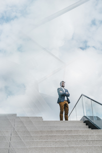 Businessman standing atop of stairsの写真素材 [FYI04344796]