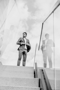 Businessman standing atop of stairsの写真素材 [FYI04344798]