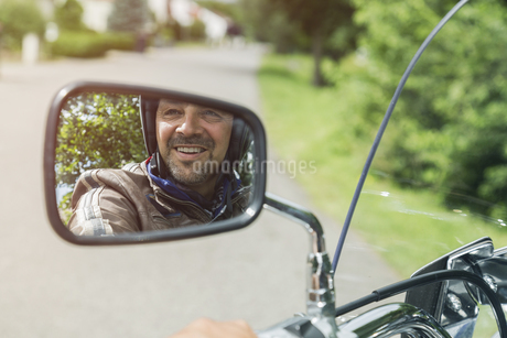 Reflection of smiling man in mirror of motorbikeの写真素材 [FYI04344803]