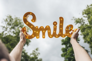 Man holding aloft the shining word 'Smile'の写真素材 [FYI04344814]