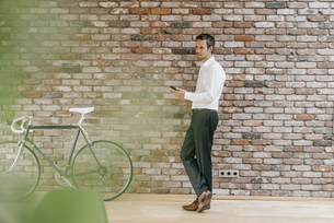 Businessman with bicycle and cell phone at brick wallの写真素材 [FYI04344997]