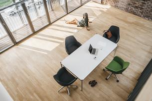 Top view of woman sitting on the floor in boardroomの写真素材 [FYI04345001]