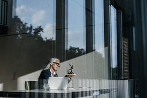 Businesswoman at desk looking at sculptureの写真素材 [FYI04345018]