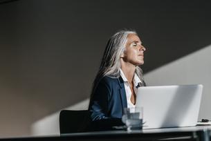 Businesswoman at desk enjoying sunlightの写真素材 [FYI04345019]