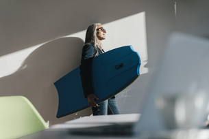 Businesswoman in office holding surboard enjoying sunlightの写真素材 [FYI04345020]