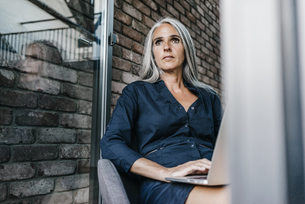 Woman with long grey hair using laptopの写真素材 [FYI04345024]
