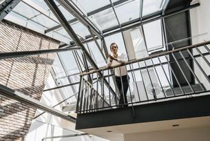 Businessman standing on upper floor in officeの写真素材 [FYI04345031]