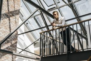 Businessman standing on upper floor in officeの写真素材 [FYI04345032]