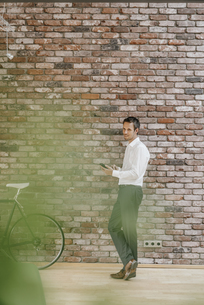 Businessman with bicycle and cell phone at brick wallの写真素材 [FYI04345045]