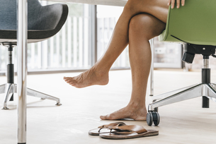 Woman sitting in office with bare feetの写真素材 [FYI04345055]