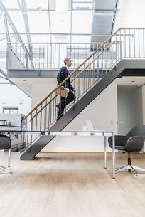 Businessman walking on stairs in a loftの写真素材 [FYI04345089]