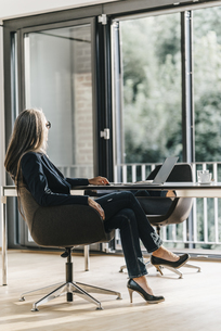 Businesswoman at desk with laptopの写真素材 [FYI04345095]