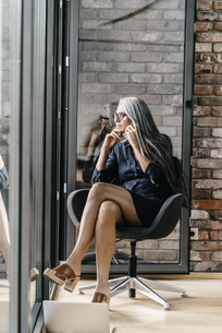 Woman with long grey hair on cell phone sitting at the windoの写真素材 [FYI04345097]
