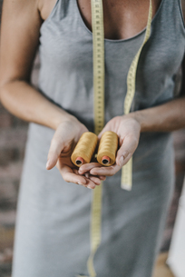 Woman with tape measure holding cotton reelsの写真素材 [FYI04345106]