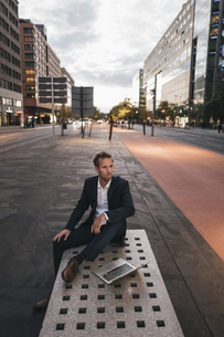 Germany, Berlin, Potsdamer Platz, businessman sitting on benの写真素材 [FYI04345158]