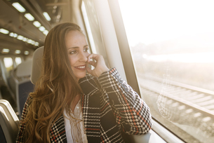 Smiling woman on a train looking out of windowの写真素材 [FYI04345181]