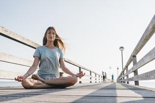 Young woman practising yoga on jettyの写真素材 [FYI04345190]