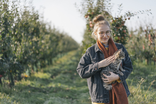 Young woman holding a cat in apple orchardの写真素材 [FYI04345255]