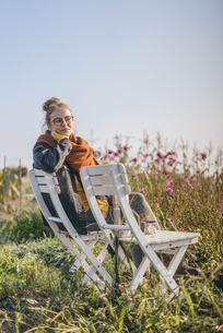 Young woman relaxing in cottage gardenの写真素材 [FYI04345287]
