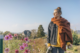 Young woman with thermos flask in cottage gardenの写真素材 [FYI04345288]